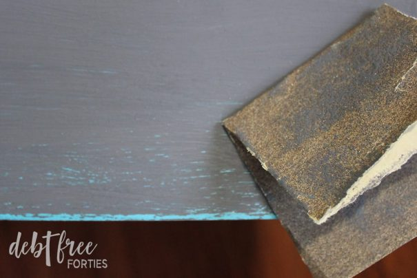 Use a high grit sandpaper to remove the top layer of paint where you've used your candle wax.