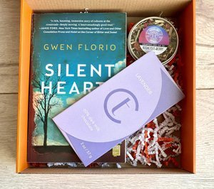 subscription box with book, chocolate and tea